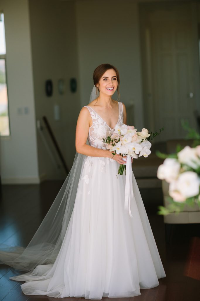 happy bride in Greta kate gown with beautiful flowers