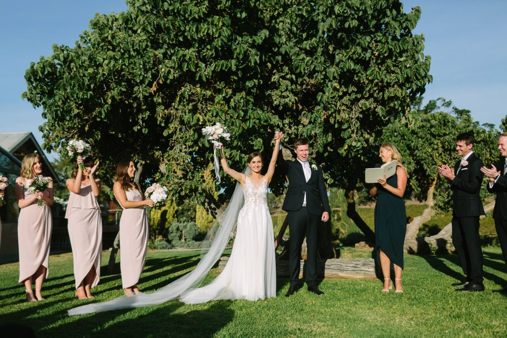 Bride and groom celebrate just married outdoors at Coriole Winery Mclarenvale
