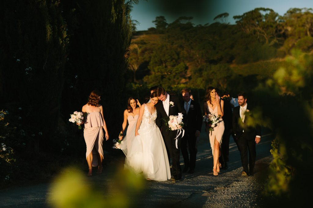 Sunset at Coriole winery wedding. Bride and groom wander through Mclarenvale with bridal party