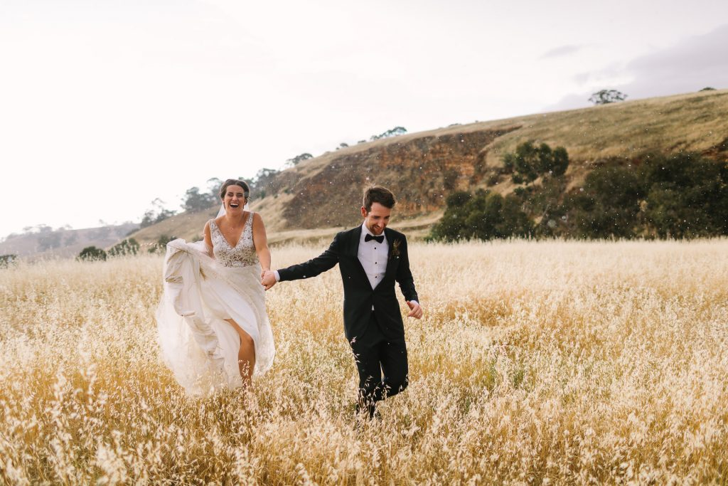 Bride and Groom running in the rain in a field at their wedding in Clare Valley South Australia