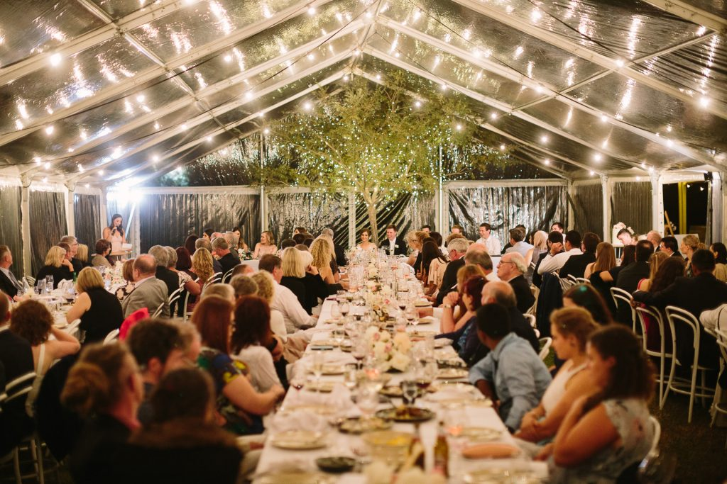 Marquee wedding reception with tree inside marquee behind the bridal table at Coriole winery in Mclarenvale