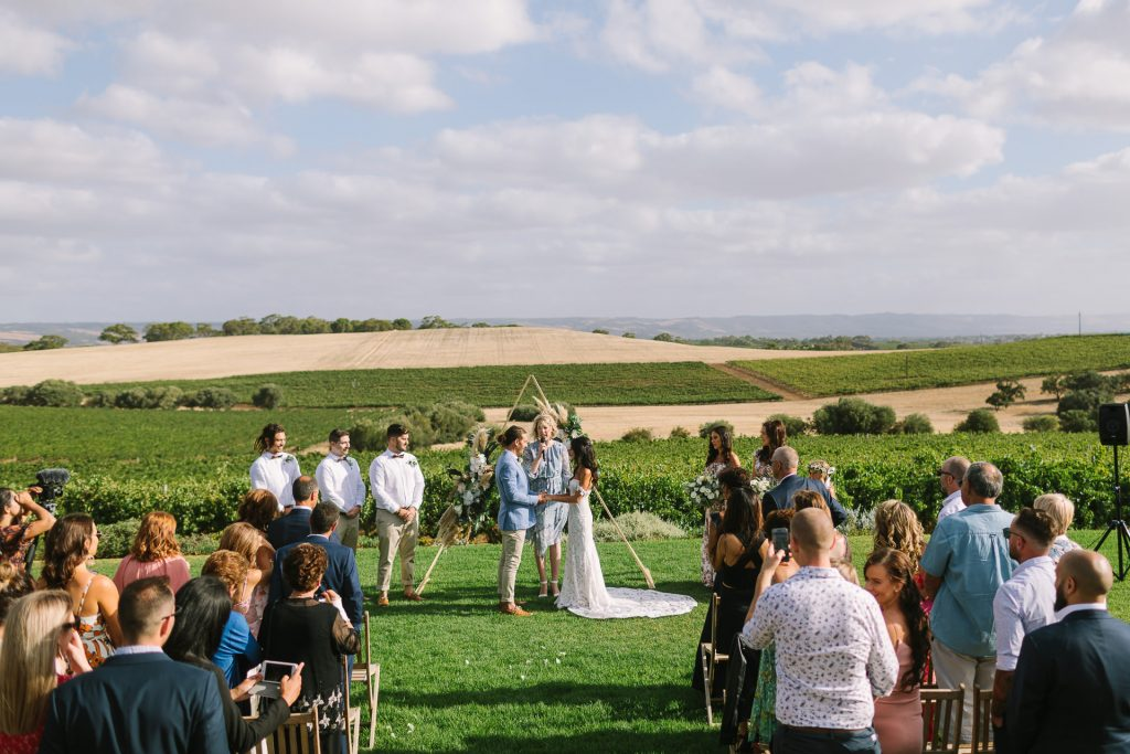 Wedding ceremony on lawn at coriole winery in Mclarenvale, overlooking vineyards