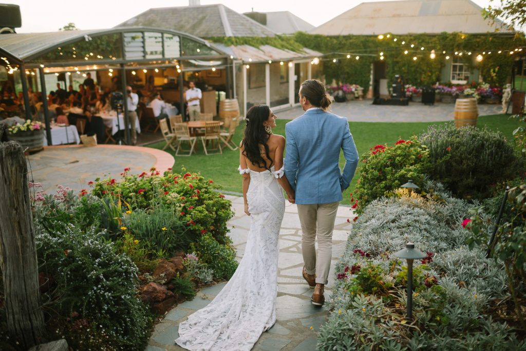 married couple walk enter their wedding reception through courtyard at coriole winery in Mclarenvale