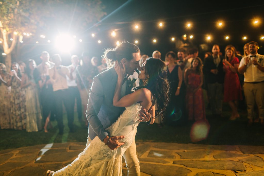 Bride and groom enjoy their first dance at their wedding on the crazy pave dance floor outside, in the open air courtyard, under festoon lights, surrounded by all their guests.