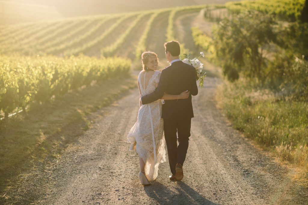 Beautiful bride and dapper groom walk away as bride looks back to Dave Pascoe photographer in vineyard at Coriole winery in Mclarenvale