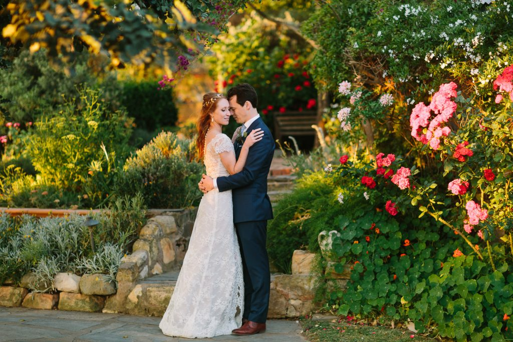 married couple in amongst beautiful flowers in bloom at Coriole winery in Mclarenvale