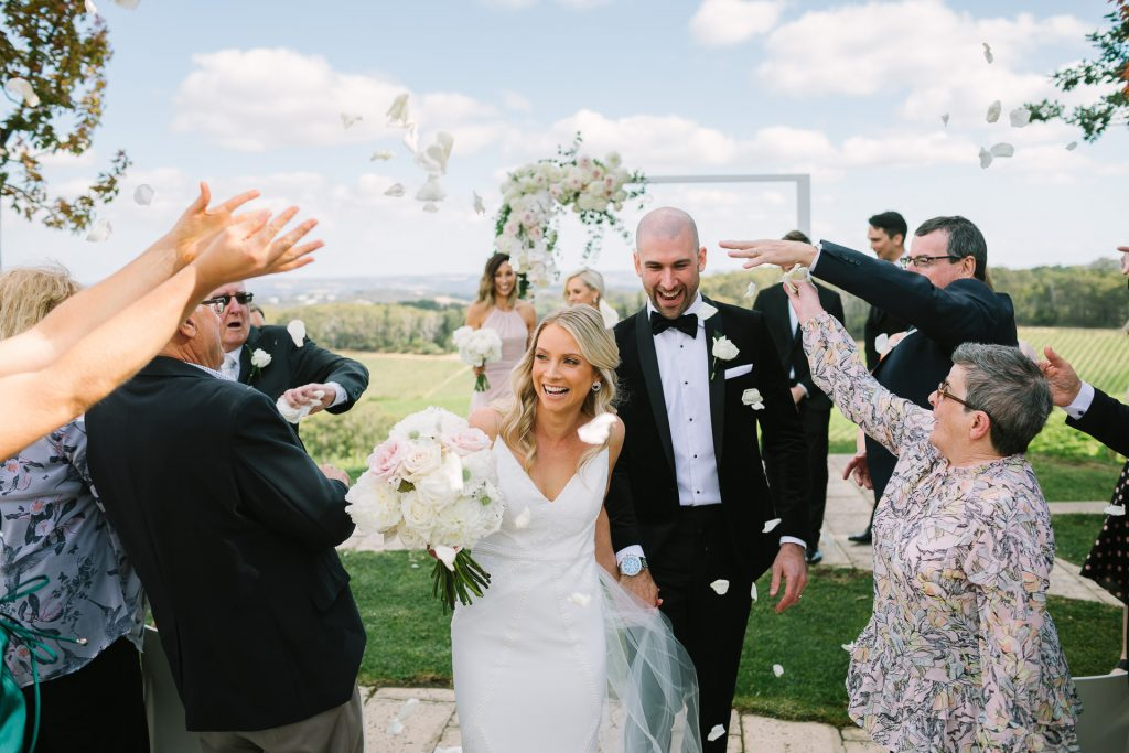 Happy bride and groom walk down the aisle showered in flower petals by guests at Wedding ceremony at Pike and joyce winery in the adelaide hills