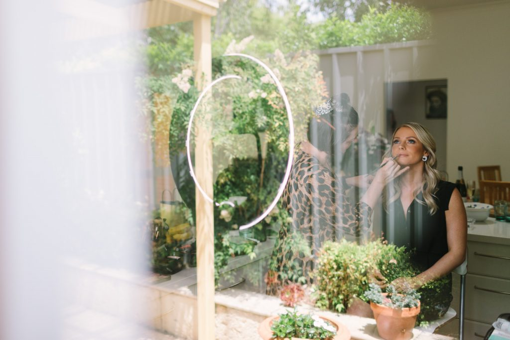 Bride getting make up done with reflections in the window of her garden