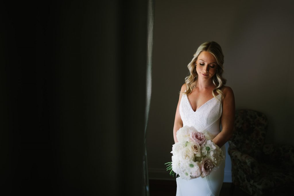 bride in Bride Lab dress poses in beautiful window light for portrait with her bouquet of flowers in her house in Adelaide