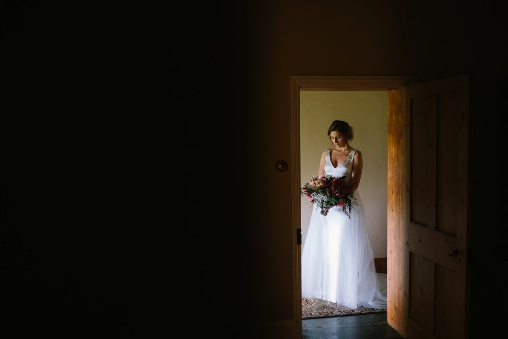 bride holding flowers in her wedding dress poses in beautiful light, framed by a doorway in the cottage at barn 1890 Willunga, Mclarenvale