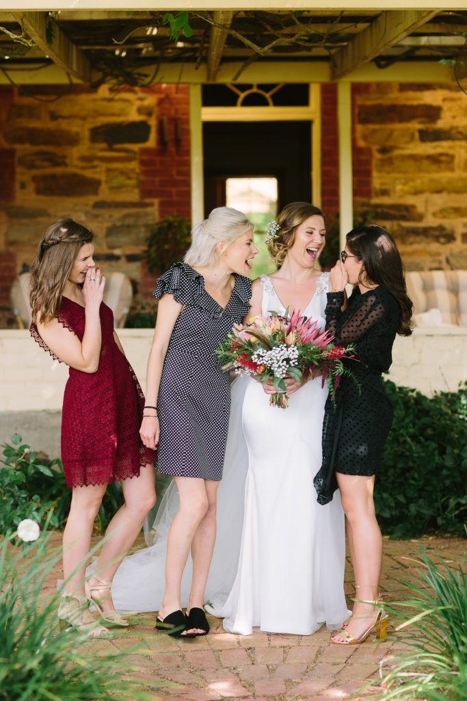 Bride with bridesmaids in mismatched dresses all laughing together in front of the cottage at barn 1890 willunga