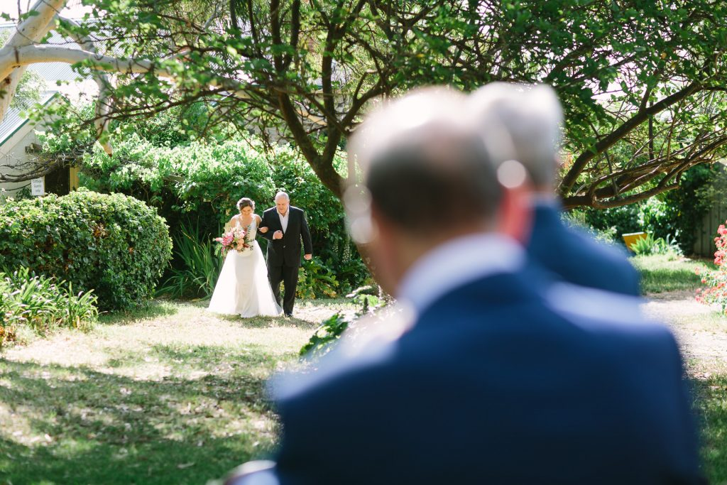 bride walks down the aisle at outdoor ceremony in the garden at Barn 1890 near willunga, mclarenvale