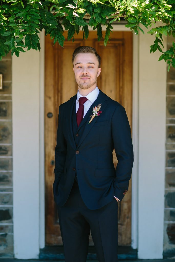 dapper groom in navy suit poses for portrait