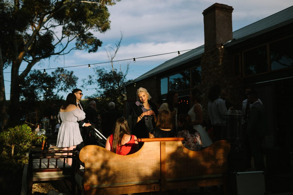 Sun goes down as guests enjoy drinks and canapes outside Barn 1890 wedding reception Willunga