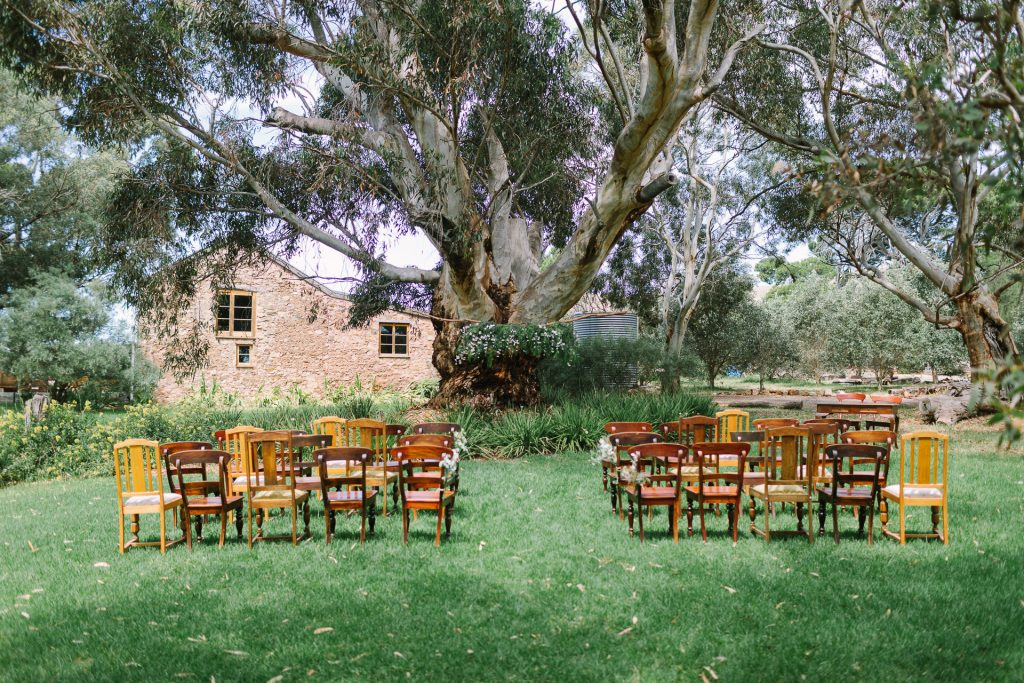 Barn 1890 in Willunga / sellicks , ceremony setup with wooden chairs and floral arrangement