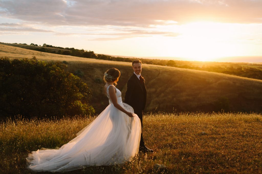 Bride and groom walk through a field in Willunga hand in hand at dusk as the sunset explodes behind them