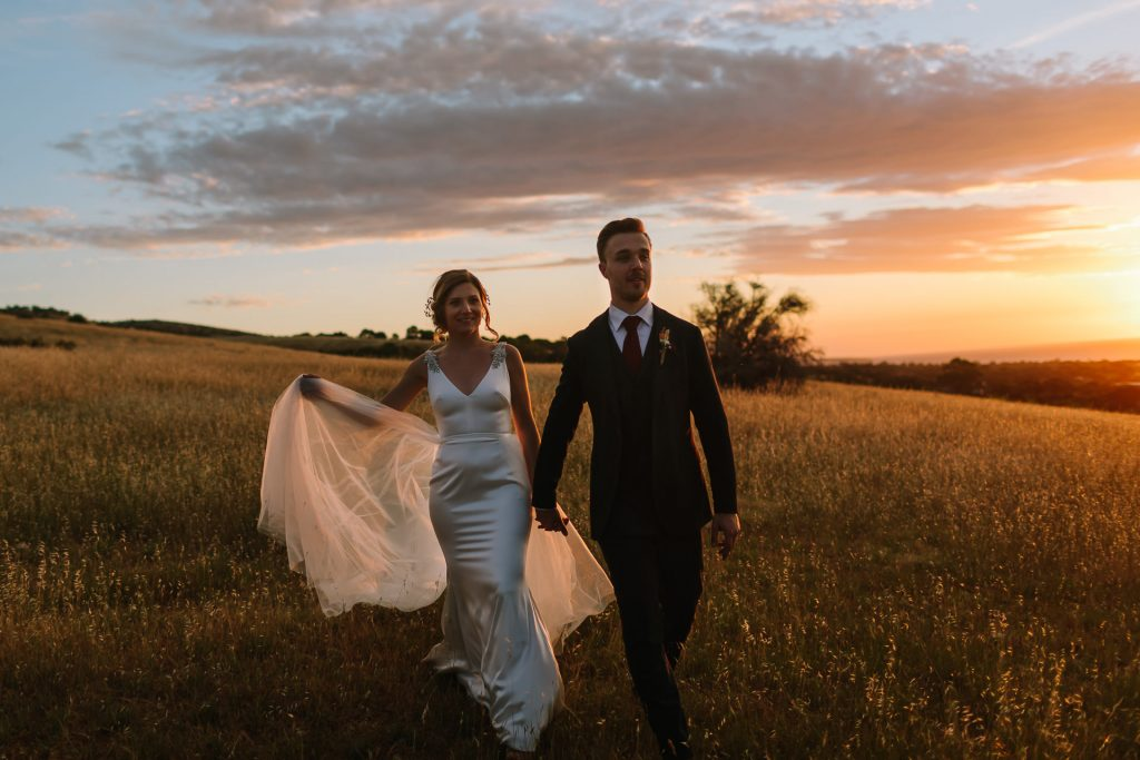 Bride and groom walk through a field in Willunga hand in hand at dusk as the sunset explodes behind them Barn 1890 Mclaren Vale wedding