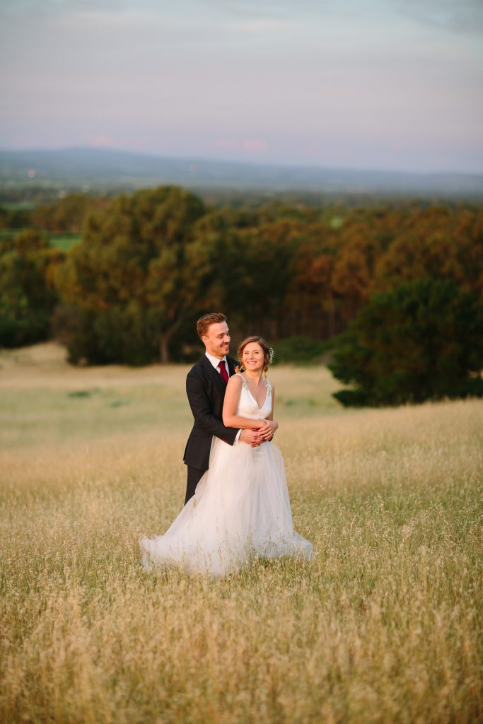 Bride and groom in field at sunset near Willunga