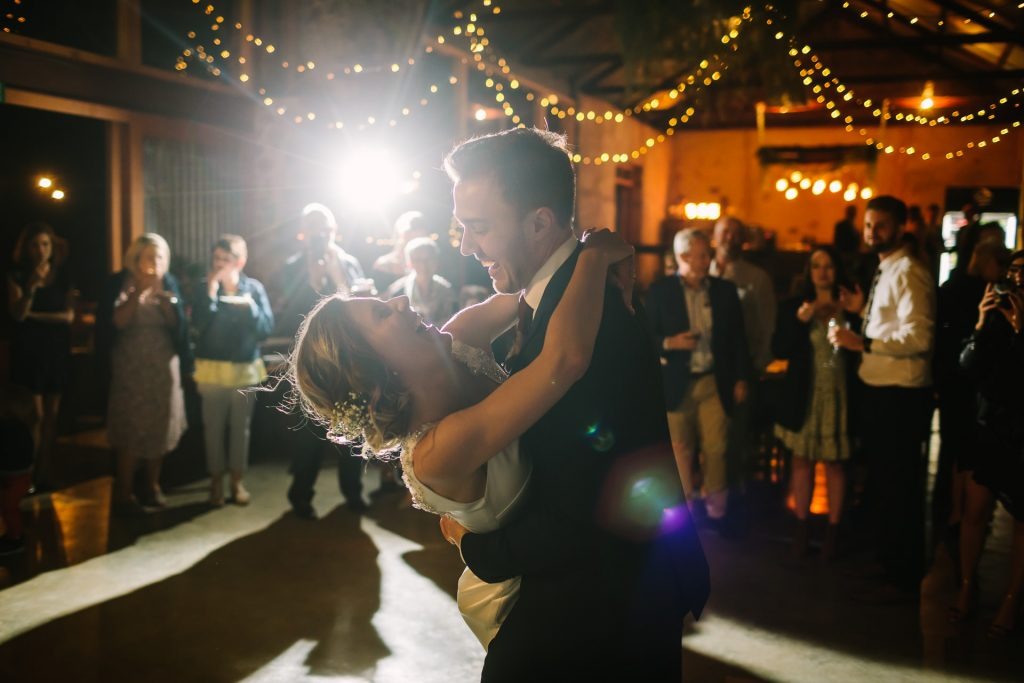 Groom Dips bride during their first dance as guest look on under fairy lights at Barn 1890 in Willunga