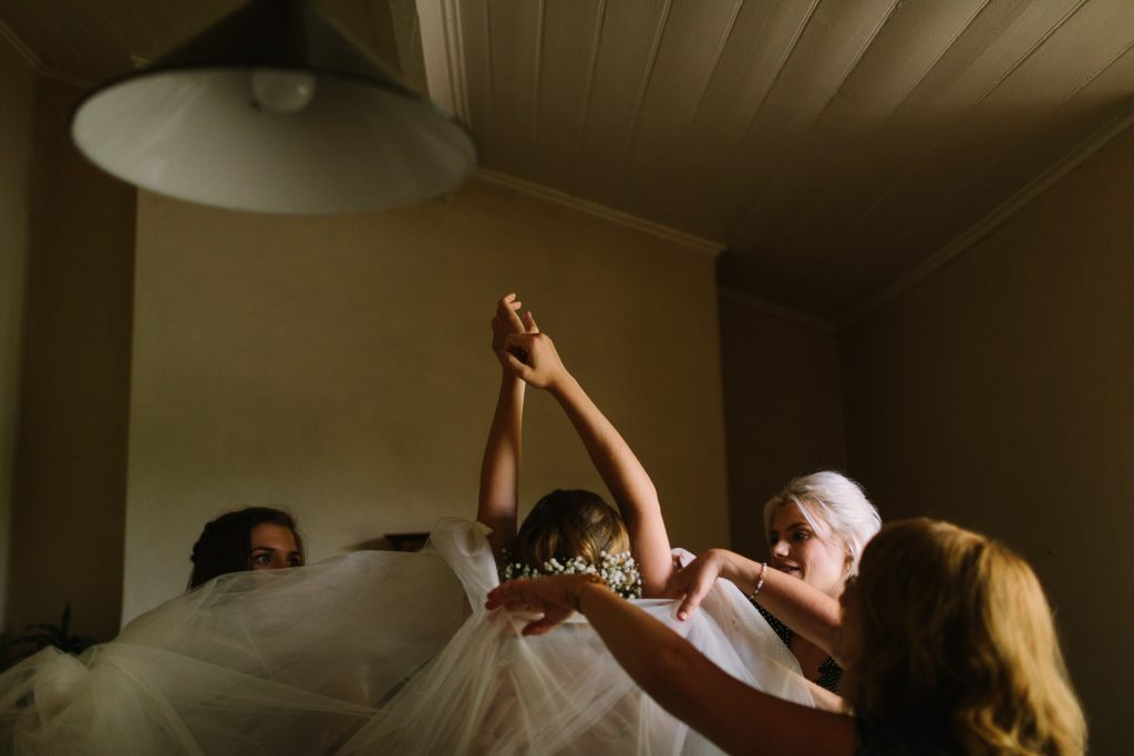 Bride getting into her dress with bridesmaids at the cottage at Barn 1890 wedding