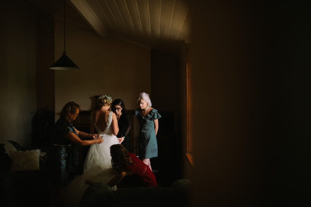 Bride getting into her dress and preparing with bridesmaids at the cottage at Barn 1890 wedding