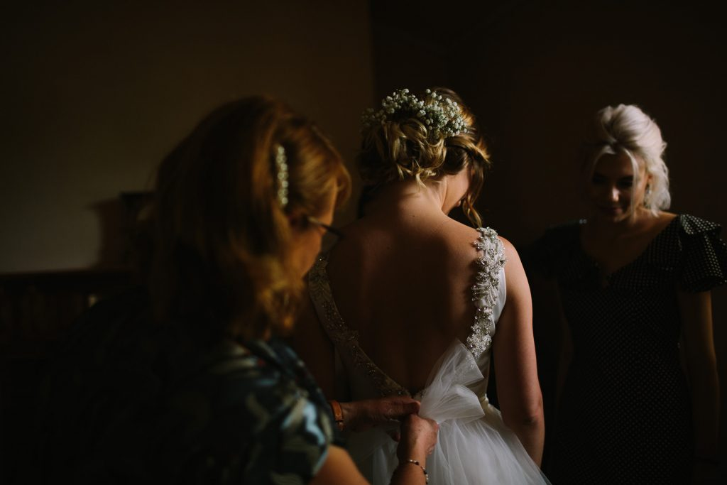 Bride getting help with the back of her dress with bridesmaids at the cottage at Barn 1890 wedding
