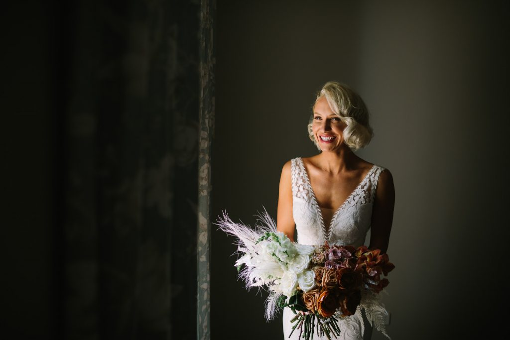 Bride in window light with flowers at kingsford homestead