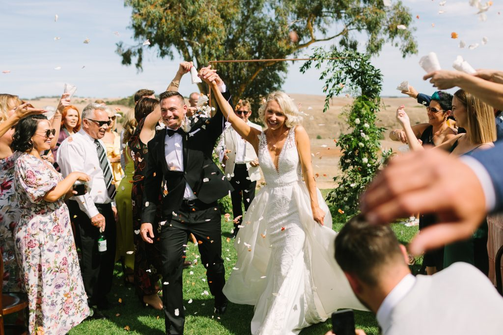 Bride and groom celebrate and walk down the aisle smiling as guests throw petals at their Kingsford Homestead wedding ceremony in the Barossa Valley