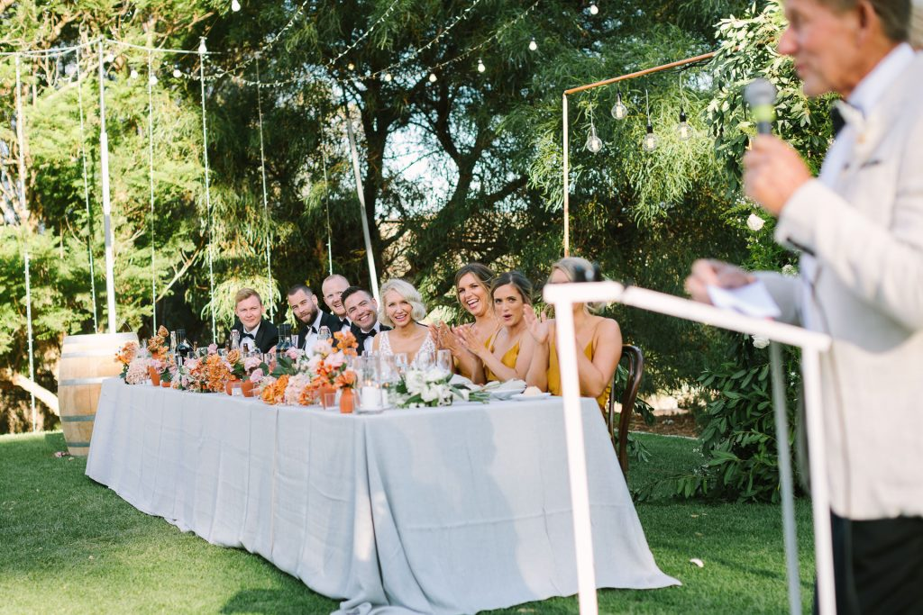 Bridal party laugh together on bridal table at reception at Kingsford Homestead wedding in the Barossa Valley