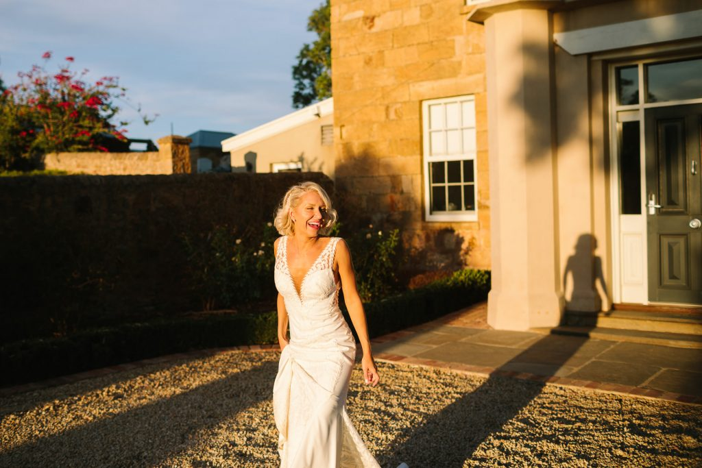 Bride laughs as she strides out of Kingsford homestead in beautiful late afternoon sunlight on her wedding day