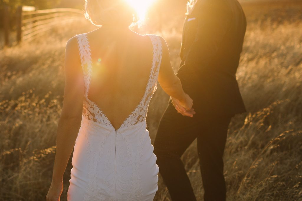 Bride and groom location photos in golden sunset light on their wedding day in the fields above Kingsford Homestead  in the Barossa Valley