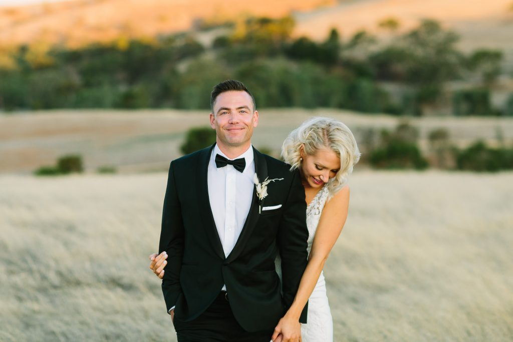 Dapper Groom in black tie with his new bride in a field at dusk - Kingsford Homestead Barossa Valley