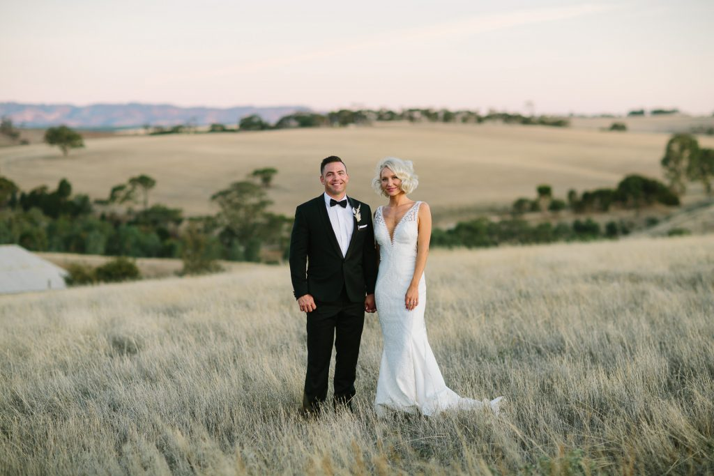 Bride and groom stand hand in hand at dusk in a field at their kingsford homestead wedding