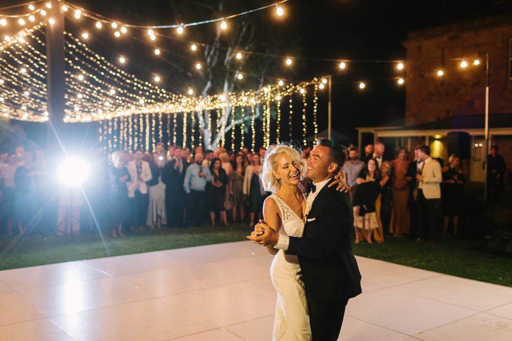 Bride and groom first dance at Kingsford homestead wedding under festoon lights open air dance floor